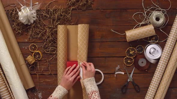 Thumbnail for Hands of Woman Packing Christmas Present on Wooden Table