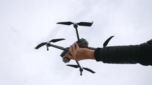 Low View To Quadcopter Tacking Off From Male Hand
