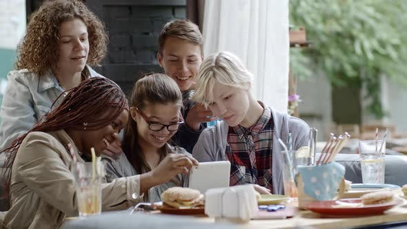 Cover Image for Company of Teenagers Using Digital Tablet in Outdoor Cafe