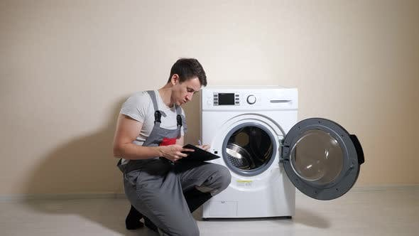 Worker Checks Broken Washing Machine and Makes Notes in Room