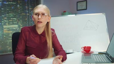 Pretty Blonde Woman Teaching By Speaking to the Camera