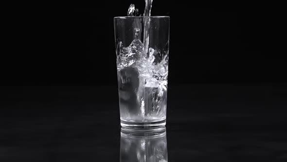 Thumbnail for Water Pours into a Glass with Splashes on a Black Background