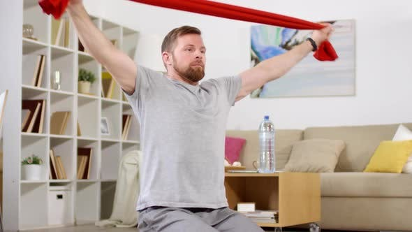 Thumbnail for Man Exercising with Resistance Band at Home
