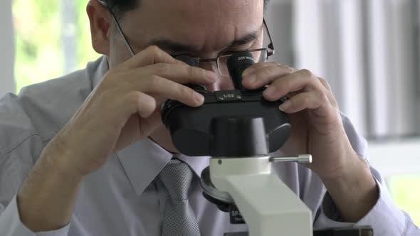 Scientist man is looking through microscope