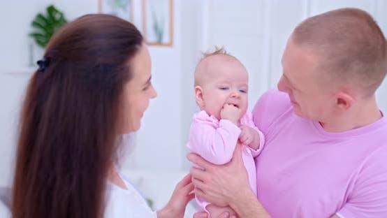 Porträt eines neugeborenen Babys in Papas Armen. Schönes Kind hält eine Faust in seinem Mund, saugt seine