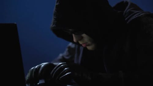 Strange Man in Black Clothes, Sunglasses and Gloves Stealing Data From Laptop