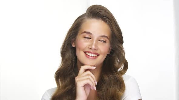 Thumbnail for Cute Girl with Healthy Long Curls Smiling with Flirtatious Look