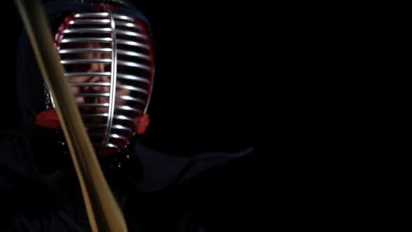 Thumbnail for Masculine Kendo Warrior Practicing Martial Art with the Bamboo Bokken on Black Background. Slow