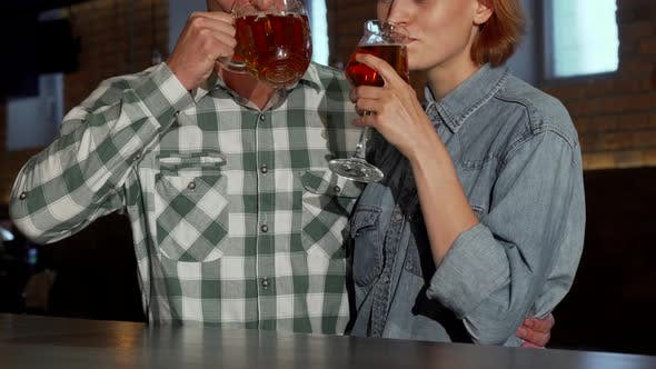 Cover Image for Lovely Couple Embracing While Drinking Beer Together at the Restaurant