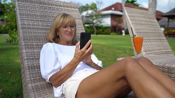 Woman Over 50 on a Sunbed Smiling at Her Smartphone While Video Calling with Beloved Ones