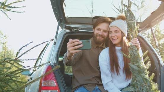 Thumbnail for 30-Aged-Paar, das Foto mit schönem Weihnachtsbaum nahm, wählten sie in der Forstwirtschaft im Stamm
