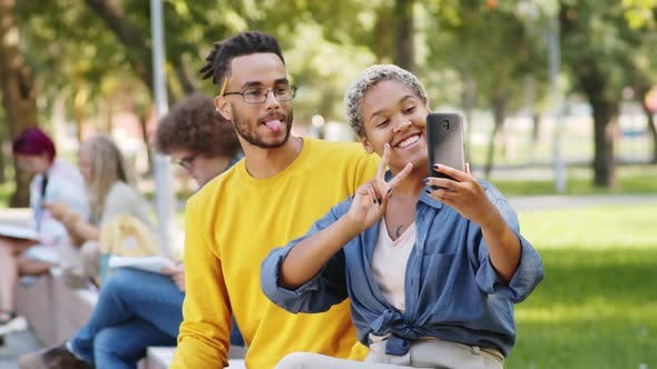 Thumbnail for Cheerful Male and Female College Students Taking Selfie in Park