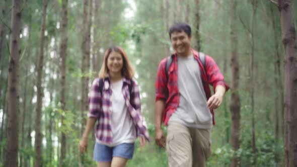 Hiker Asia backpacker couple on hiking adventure feeling freedom walk in forest their holidays.