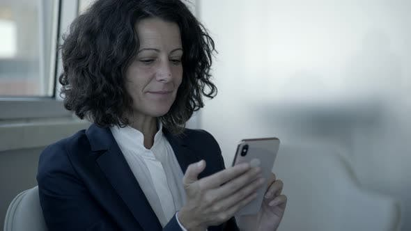 Thumbnail for Smiling Businesswoman Using Smartphone
