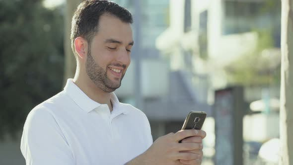 Thumbnail for Smiling Bearded Man with Smartphone Posing During Sunny Day