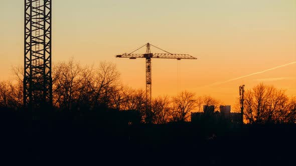 Cover Image for Tower Crane Working on Construction Site Orange Evening Sky Trees Trembling in the Wind, Golden Hour