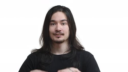 Closeup of Handsome Asian Guy with Long Dark Hair Rocker Outfit Shaping Heart Gesture in the Air and