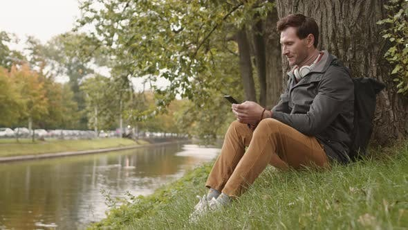 Thumbnail for Man Sitting on Grass by Tree