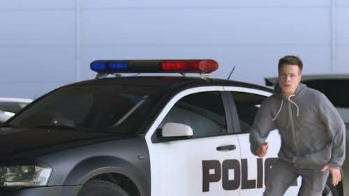 Polizist zielt auf laufende Kriminelle im Hoodie, Inhaftierung des Diebes, Slow-Mo