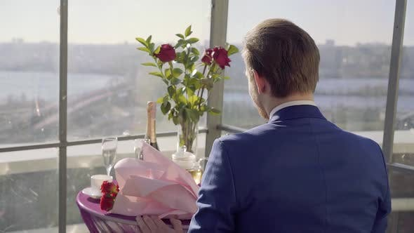 Thumbnail for Restaurant Table on the Roof with Amazing River Wiev, Man in Suit Sit on This Table with Roses