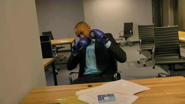 Sporty Fighty Leader in Business Concept. Afro-American Businessman Sitting with Boxing Gloves in