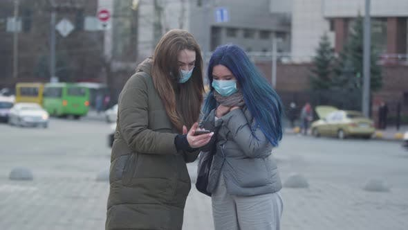 Thumbnail for Brunette Woman in Protective Mask Showing Latest News About Coronavirus To Friend on Smartphone