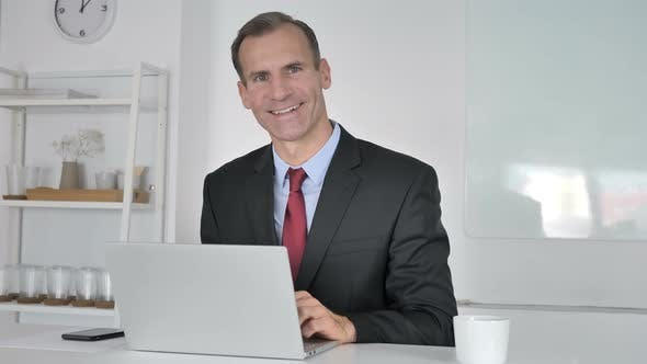 Thumbnail for Portrait of Smiling Middle Aged Businessman Looking at Camera