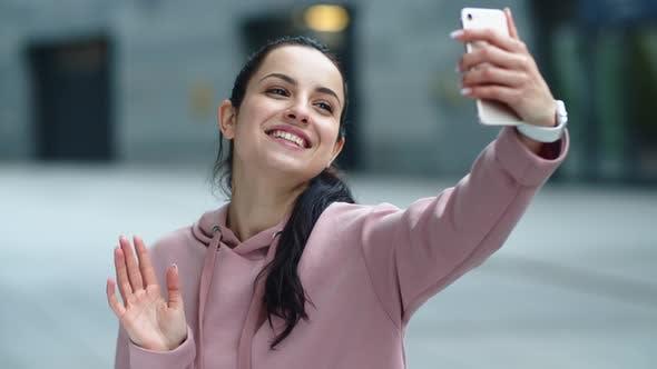 Thumbnail for Nahaufnahme lächelnde Frau winkt Hand zu Kamera. Happy Girl mit Handy
