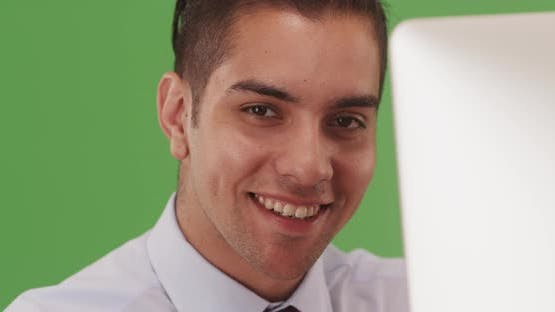 Young business professional working on cell phone on green screen