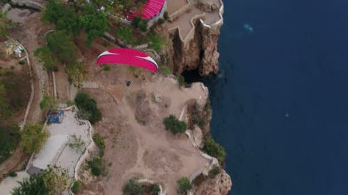 Paragliding Over Sea And Rocks Aerial Top View