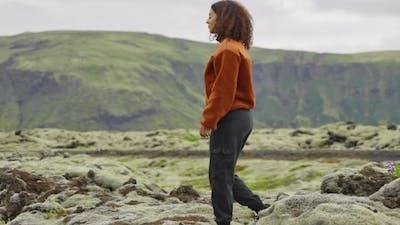 Woman Walking In Rocky Moss Covered Landscape