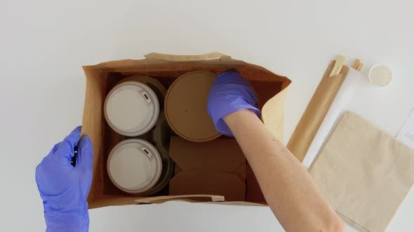 Hands in Gloves Packing Takeaway Food for Customer