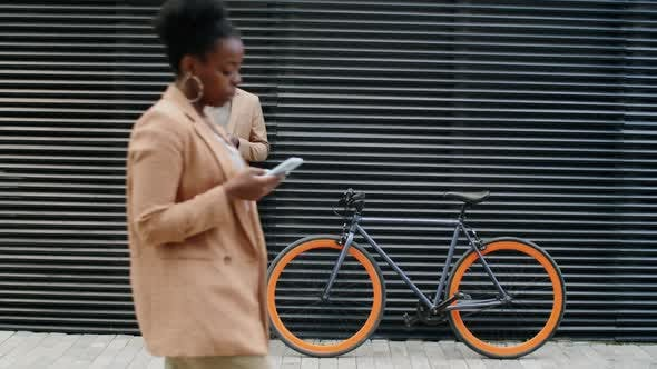 Thumbnail for Afro-American Businessman Standing by Bike and Using Smartphone