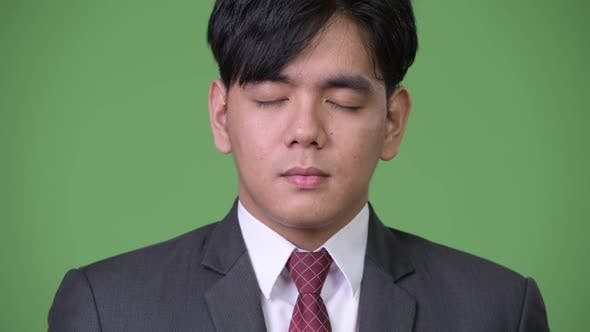 Thumbnail for Young Handsome Asian Businessman Relaxing with Eyes Closed