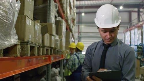 Warehouse Supervisor Checking Boxes