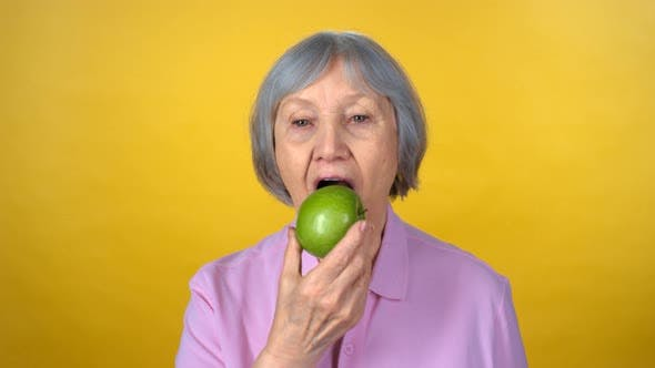 Thumbnail for Portrait of Happy Senior Woman Eating Apple