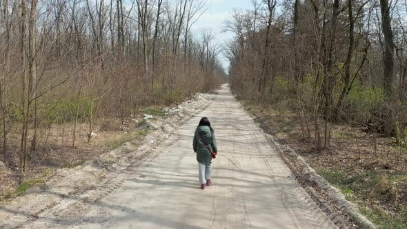 Thumbnail for Girl Walking in the Spring Forest. Copter Watches the Girl From Behind