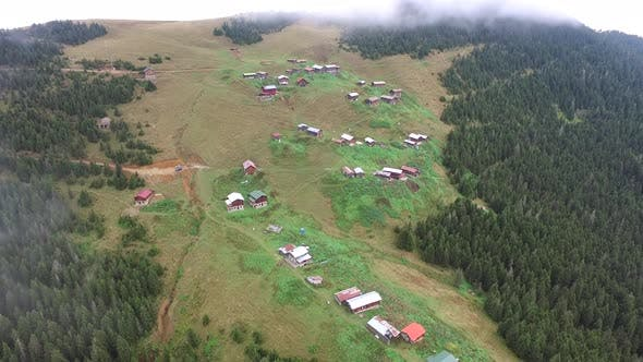 Thumbnail for Forested Mountain Village Houses Through the Clouds in Grassland
