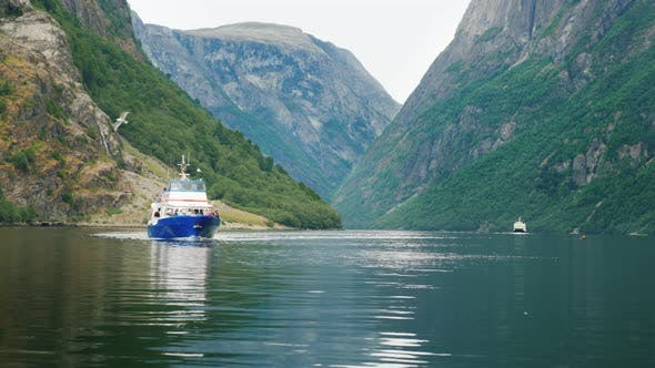 Thumbnail for A Small Cruise Ship Sails Along the Picturesque Fjord in Norway. Travel and Tourism in Scandinavia