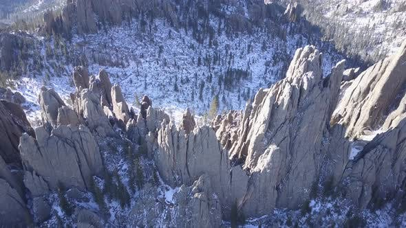 Dramatic Drone Aerial Looking Down in Forest in Winter with Pointed Rocks Spires and Needles