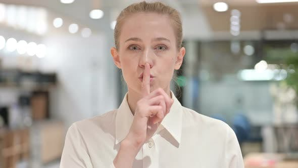 Portrait of Young Businesswoman Putting Finger on Lips, Quiet Sign