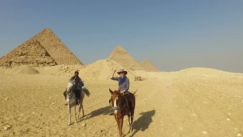 Happy woman riding horse with local man in front of Giza pyramids