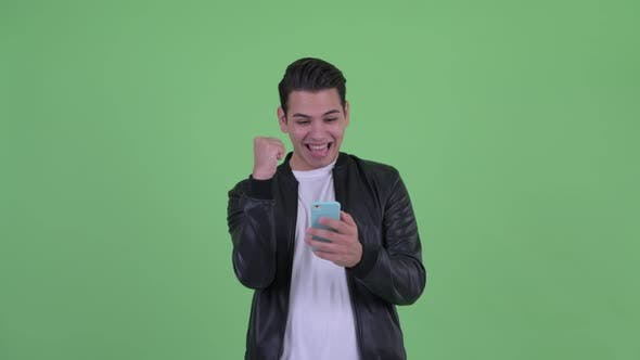 Thumbnail for Happy Young Handsome Multi Ethnic Man Using Phone and Getting Good News