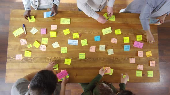 Thumbnail for Top View of Business Team Taking Off Sticky Notes from Meeting Table