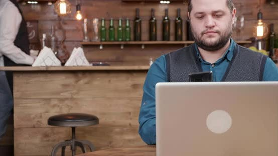 Thumbnail for Man in a Local Coffee Shop Makes a Phone Call While Drinking Coffee