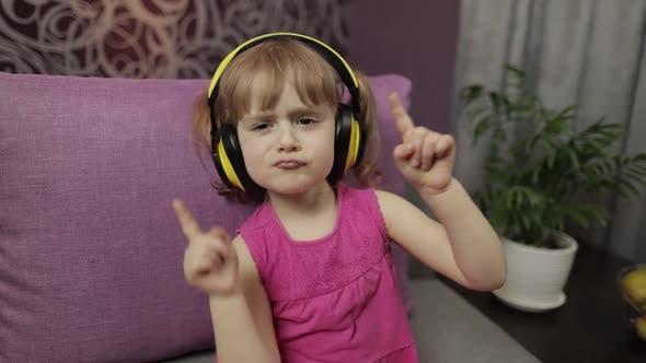 Thumbnail for Little Child Girl in Headphones Enjoying Listen Music. Dancing on Sofa at Home