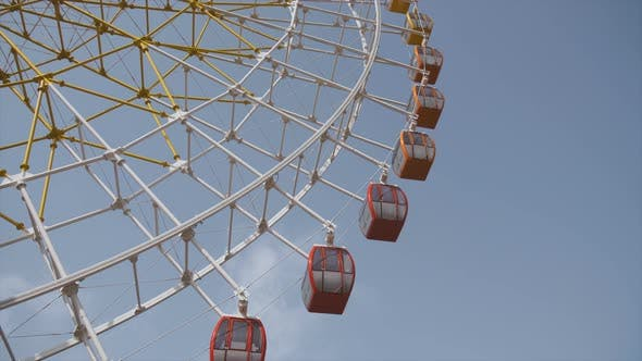 Cover Image for Big Ferris Wheel Rotates at Amusement Park Ride Over Clean Blue Sky