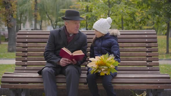 Thumbnail for Portrait of a Mature Caucasian Man in Classic Clothes Sitting on the Bench with His Granddaughter