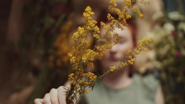 Thumbnail for Charming Redhead Woman Holding Yellow Wildflower