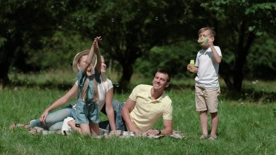 Family Day, Picnic in Nature, the Boy Plays and Blows Soap Bubbles, Young Parents and Daughter Sit